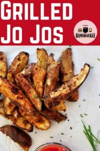 """""""Grilled Jo Jos"""" with an overhead shot of several grilled potatoes on white parchment paper and garnished with chives. Ketchup is on the side."""