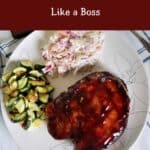 """How to Grill Pork Chops like a Boss"" with a plate of grilled goods. Coleslaw, pork chops, and zucchini."