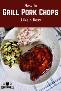 """""""How to Grill Pork Chops like a Boss"""" with a plate of grilled goods. Coleslaw, pork chops, and zucchini."""