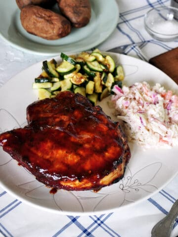 How to grill pork chops finished plate. A thick pork chop with coleslaw and zuchinni