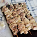 Chicken Shish Kabob on a wood plank with garlic, rosemary, and thyme in the background