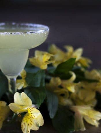 Classic margarita drink with yellow decorative flowers on a table.
