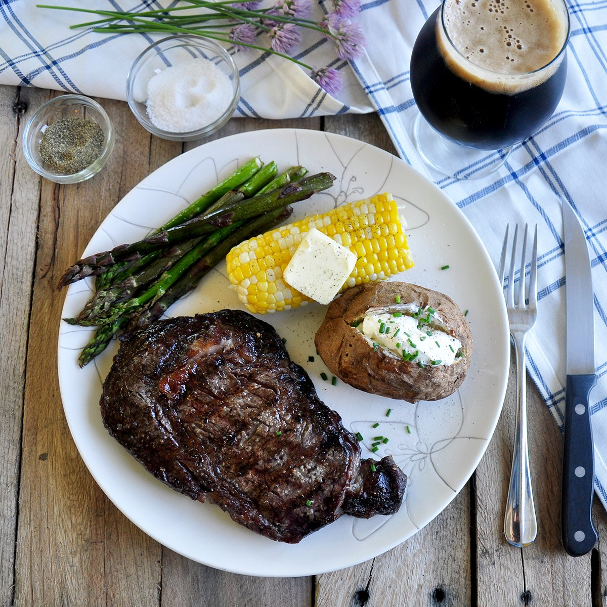 Overhead view of Ribeye Steak on a plate with a corn cob, baked potato, asparagus, and a Russian Imperial Stout