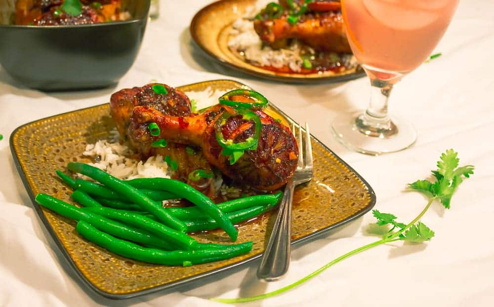 Blood Orange chicken on a plate with green beans and a drink in the background