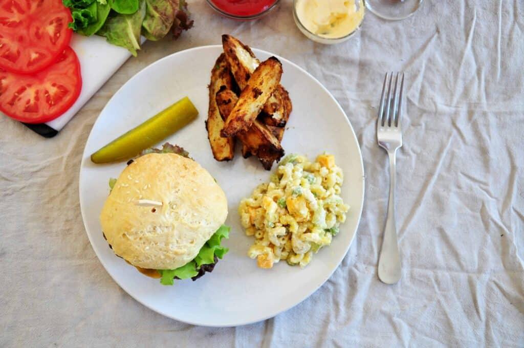 overhead burger shot on a white plate, macaroni salad, jojo potatoes, a pickle, and tomatoes
