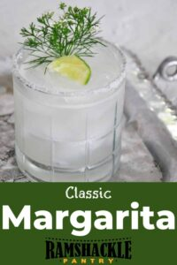 """Classic Margarita"" with a lowball glass containing the classic cocktail that is garnished with lime and dill."