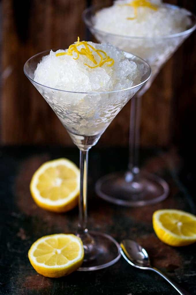 Two Prosecco Lemon and Ginger Granita dessert in cocktail glasses and garnished with lemon peel bits