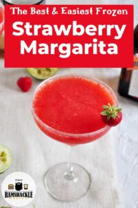 """The Best and Easiest Frozen Strawberry Margarita"""" with a drink showing garnished with sugar and a strawberry."""