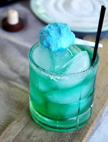 Cotton Candy Margarita on a wood plank with a small cotton candy garnish and two black straws