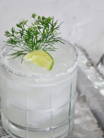 Perfect Margarita with a lime and greenery as a garnish. The lowball glass is sitting on a silver platter.