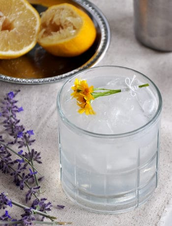 This is a Rum Daisy cocktail on a white mat with purple lavender and a few spent lemon halves in the background