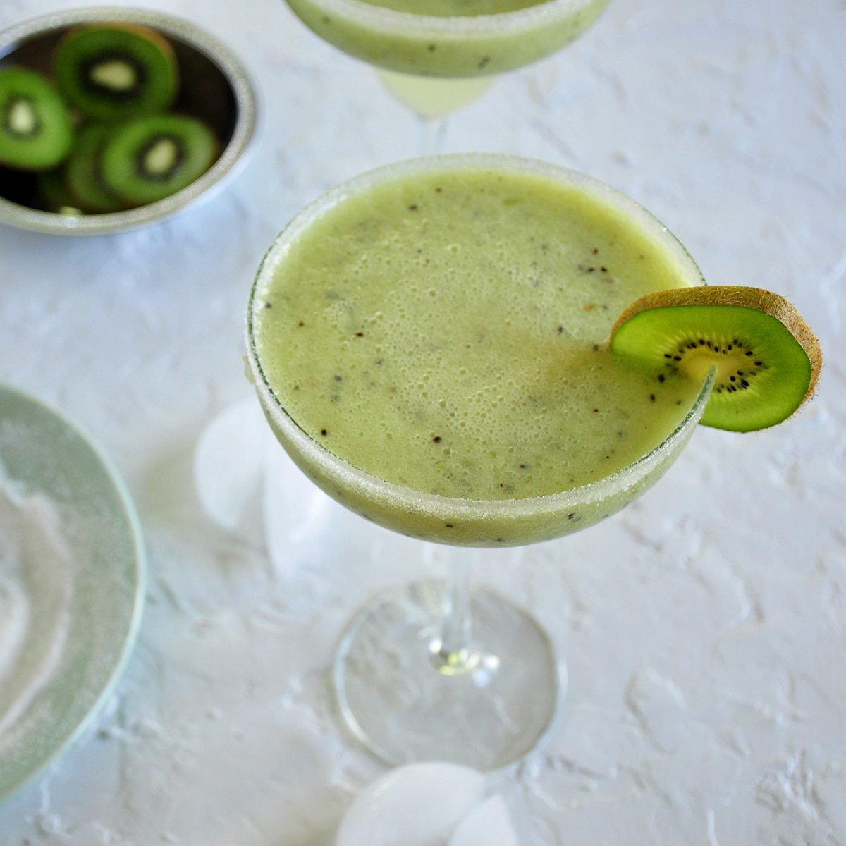 Frozen Kiwi Coconut Margarita with a kiwi slice as garnish. There is some ice laying on the board below along with a dish of sliced kiwi and a plate of sugar that was used for rimming the glass