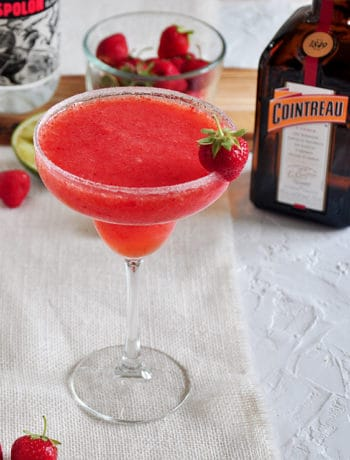 Frozen Strawberry Margarita with Cointreau and strawberries in the background