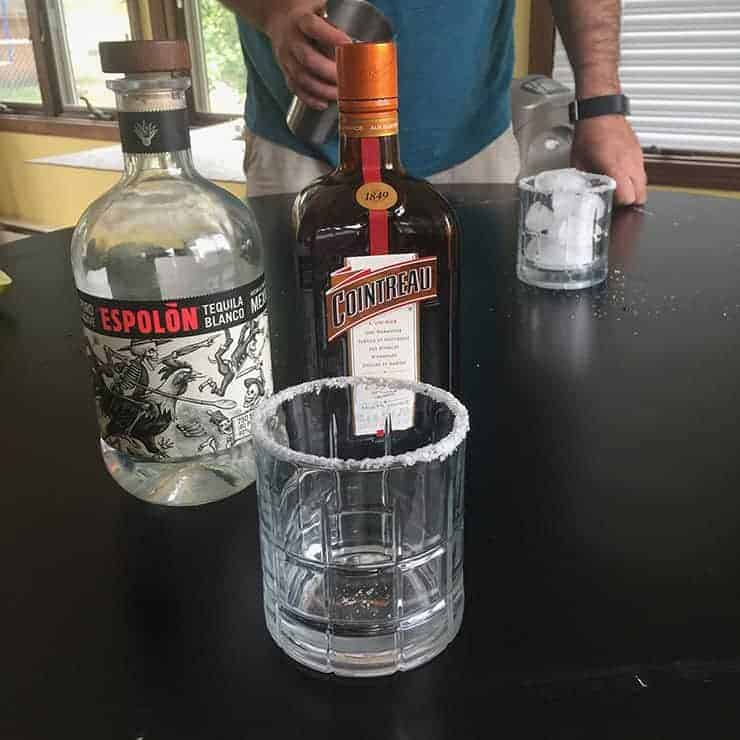 All of the liquor ingredients shown. A bottle of Cointreau, tequila, and a salt-rimmed glass.