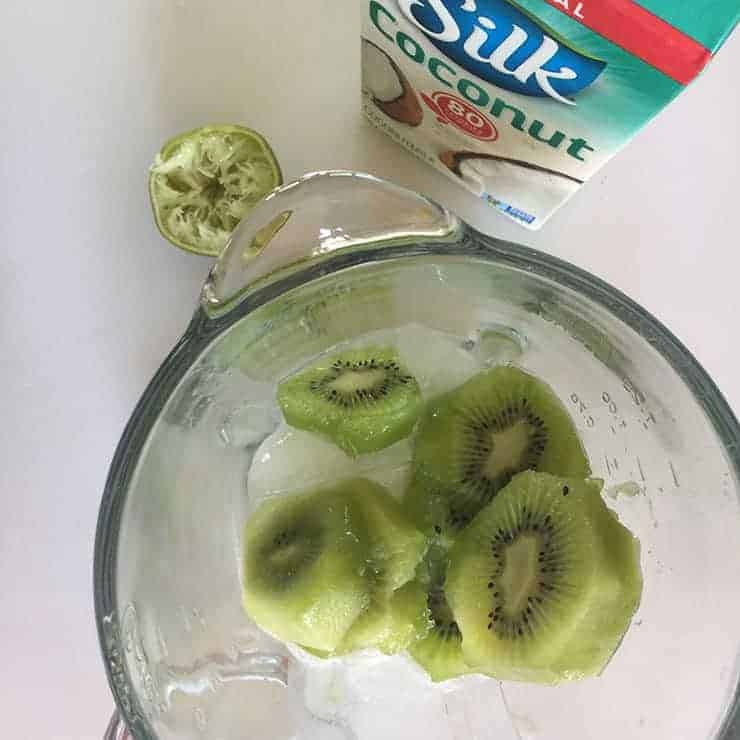 Sliced kiwi in the blender with a carton of Silk Coconut milk displayed in the background.