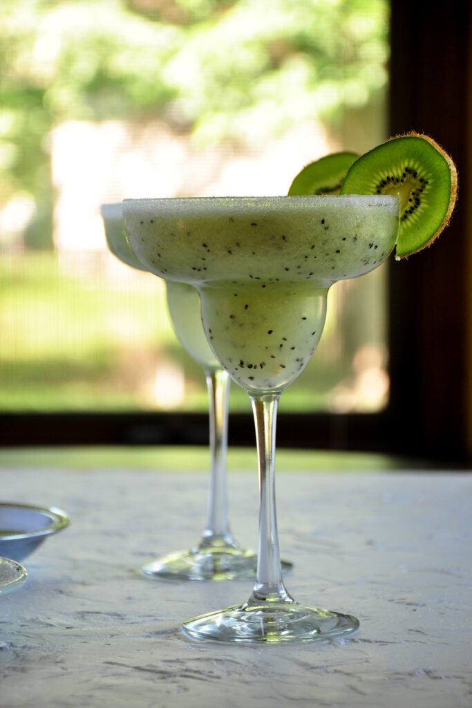 Two Frozen Kiwi Coconut Margaritas on a white platform with a window looking outside in the background. Each margarita has a kiwi slice for garnish on the margarita glass.