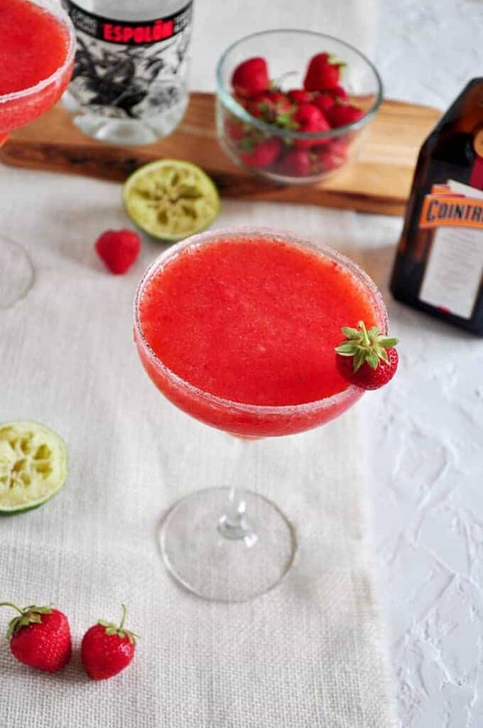 Frozen strawberry margarita on a white clothe with two strawberries, a spent lime, and a tequila bottle in the background