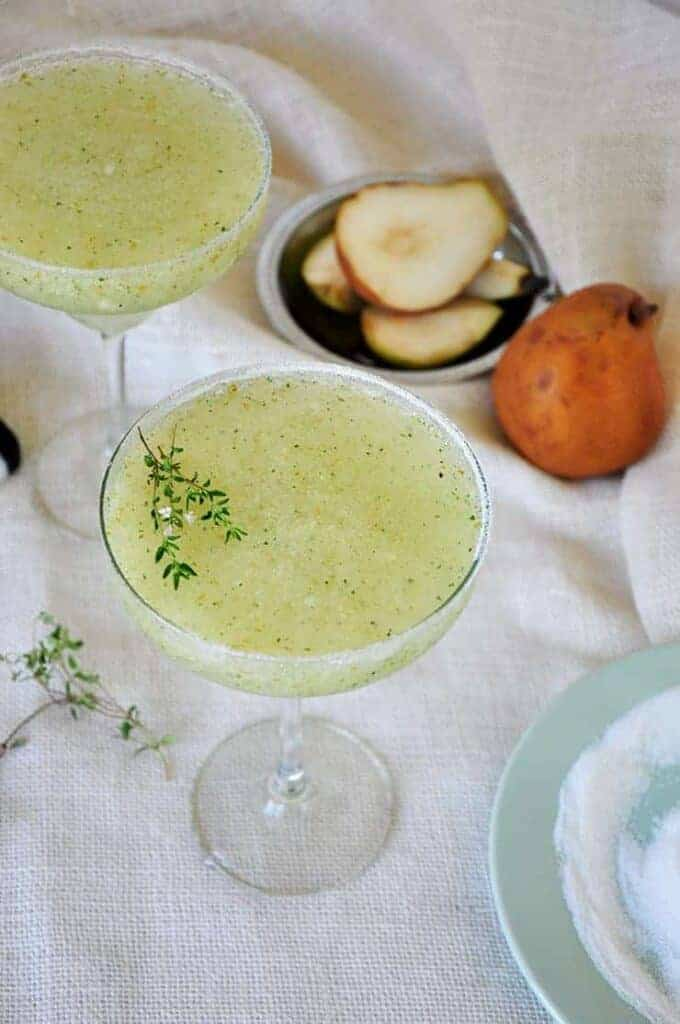 This is an image of two pear and thyme margaritas sitting on a white table cloth. There is a sliced pear in the background and a whole Bosch pear
