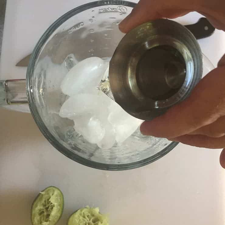 Pouring the tequila into the blender that has ice and other margarita ingredients in it