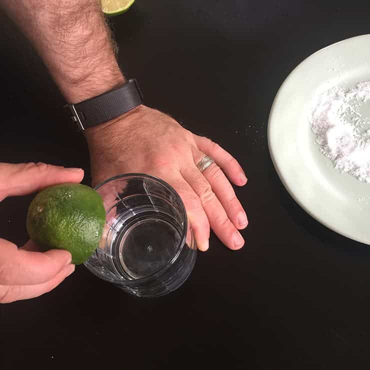 Rubbing the rim of our perfect Margarita in preparation for salting. There is a plate of salt in the same picture.