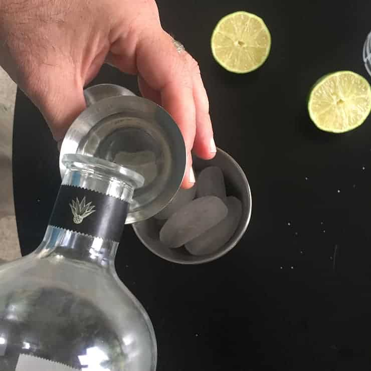 Pouring some tequila blanco into a jigger for our perfect margarita.