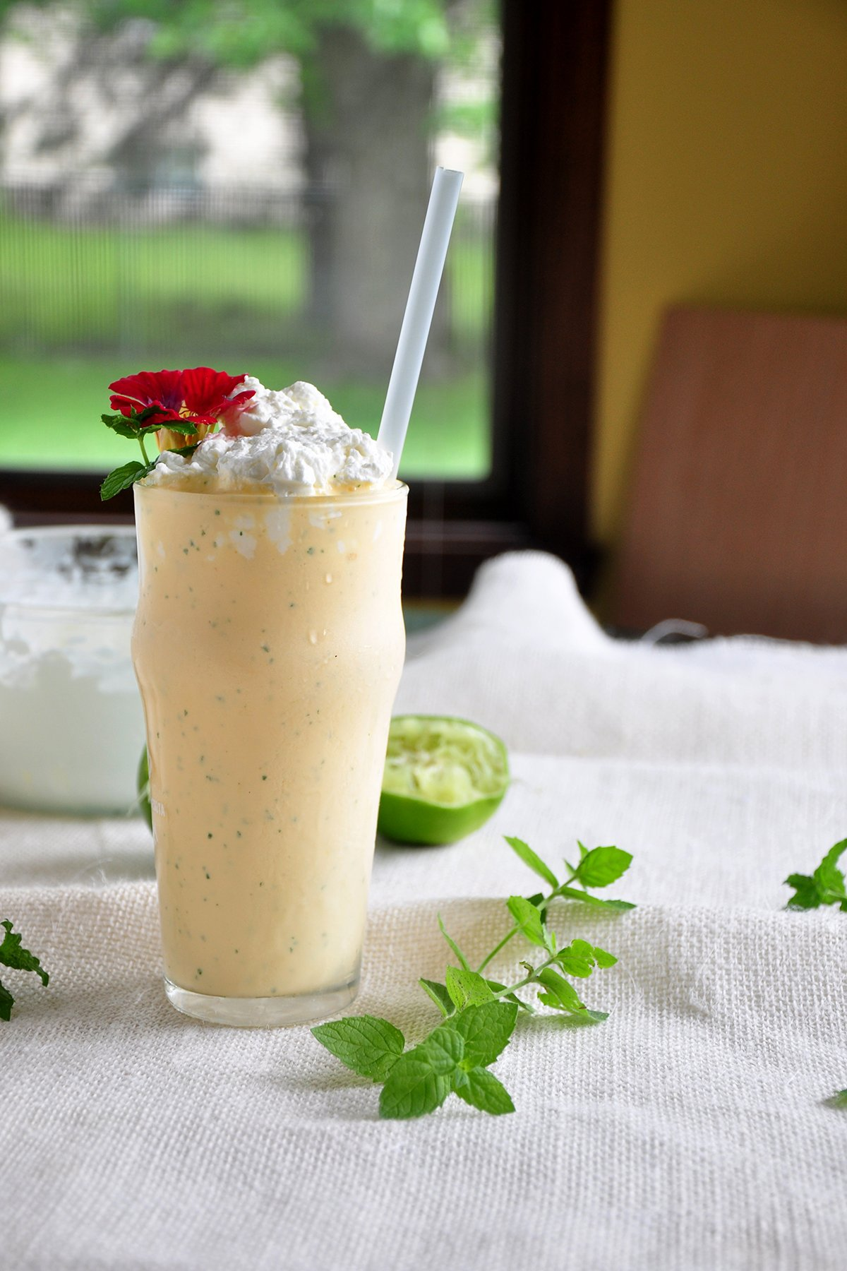 This an Ice Cream Mint Margarita and shot from the side. There is mint and lemon in the background, as well as a window.