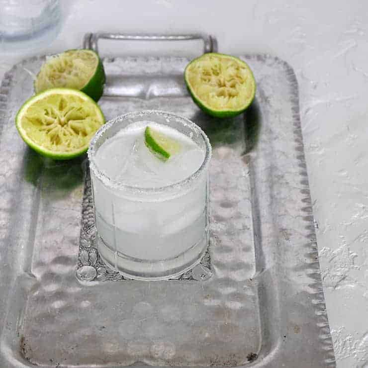 Perfect Margarita on a silver platter with three lime halves that have been juiced