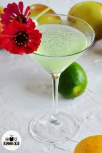 An appletini with a bright red flower as a garnish on a white backdrop, with a lime and apples in the background