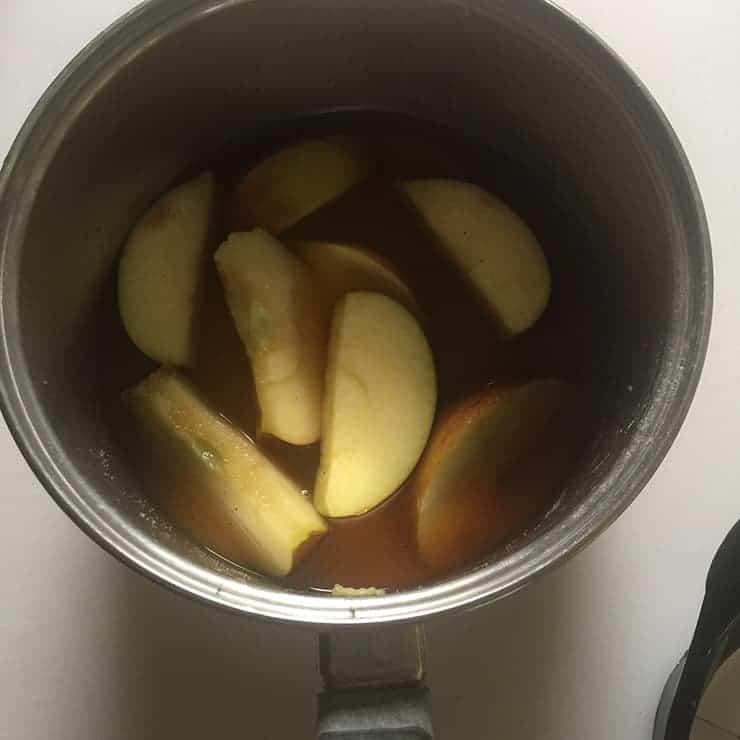 Simmering Apple Brandy liquid in saucepan
