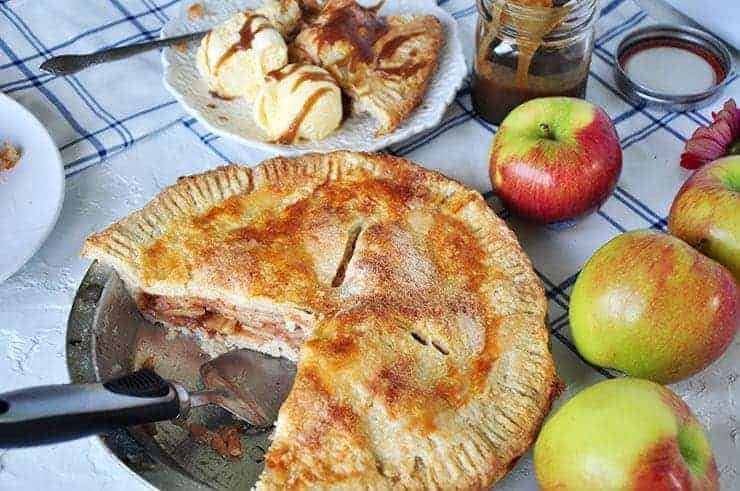 Baked apple pie with two pieces removed and placed on a plate. There is a serving utensil in the pie pan. Several Braeburn apples in the background