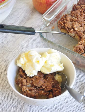Apple Crisp in a bowl with vanilla ice cream and a tray in the background