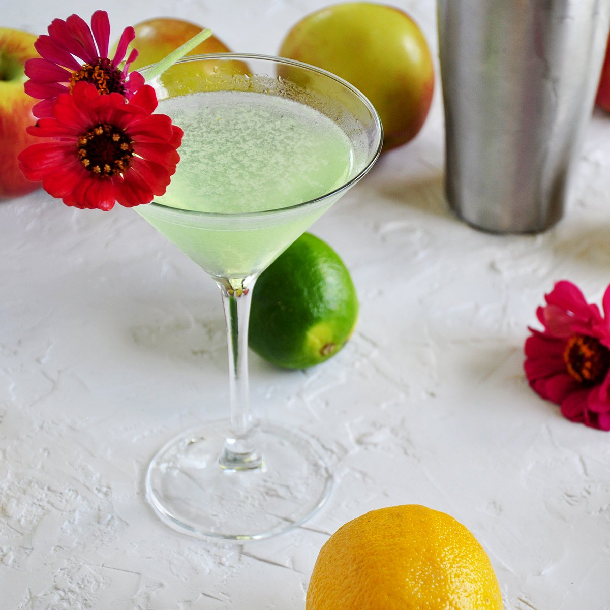 Appletini with lemons, limes, apples and flowers in the background.