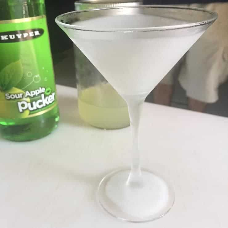 Frozen martini glass with a bottle of Apple pucker in the background