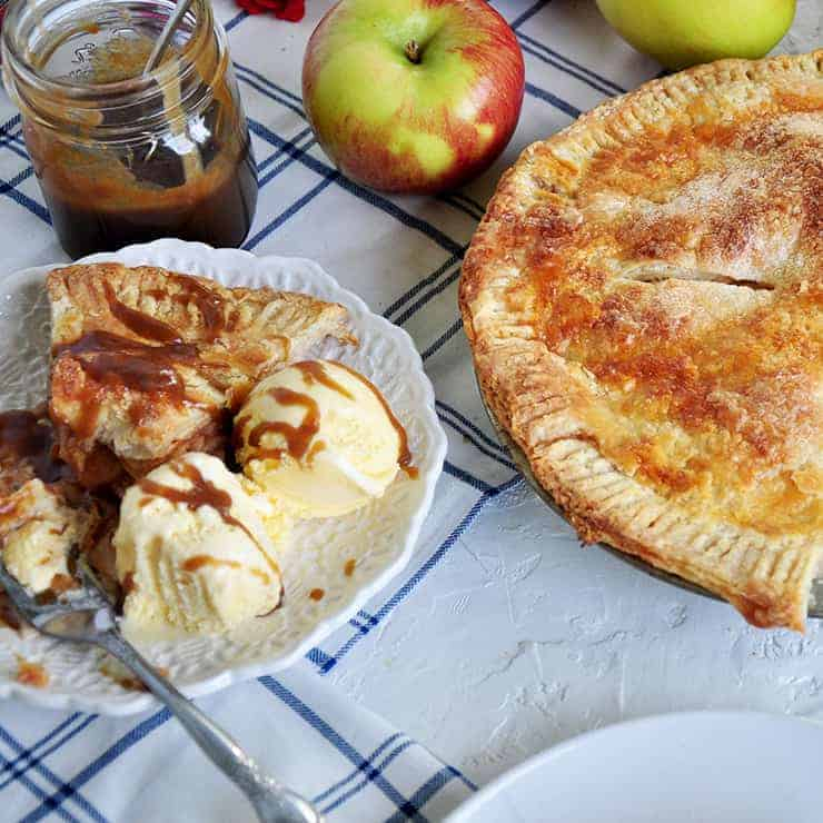 piece of apple pie with caramel and ice cream. Int he background , there is a whole pie, some Braeburn apples and some caramel.