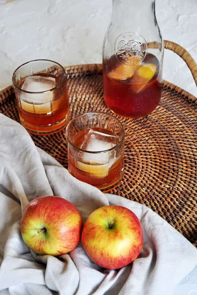 Carafe of apple brandy on a platter. Two Braeburn apples showing
