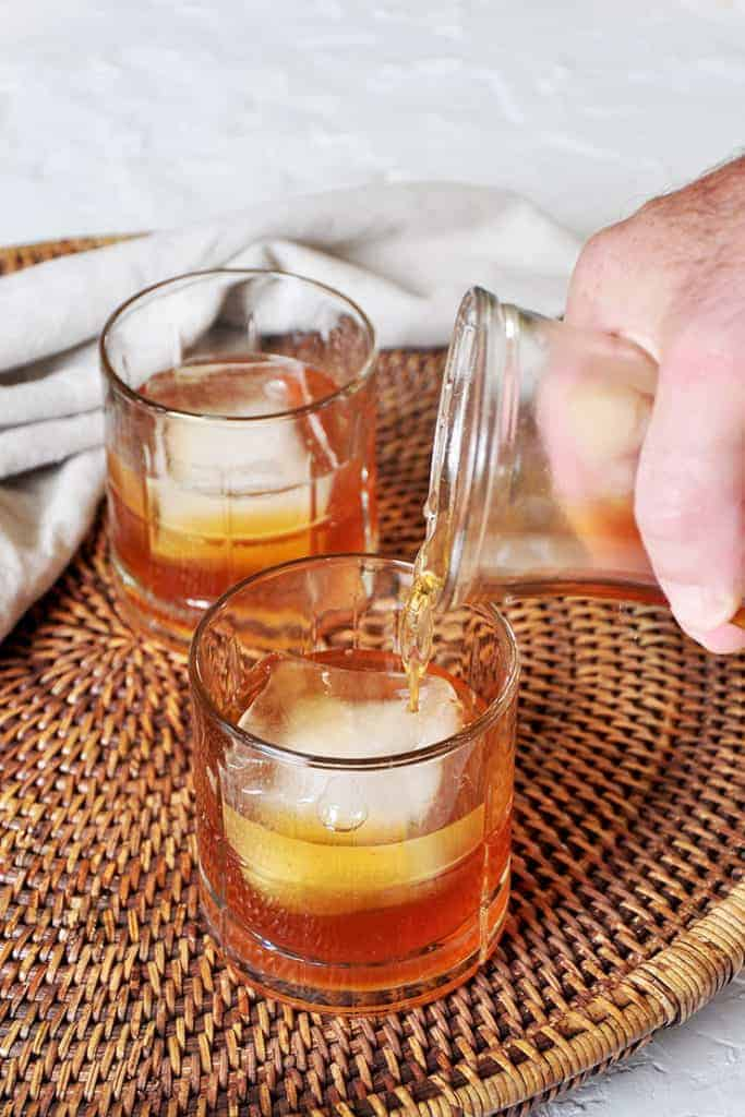 Pouring apple brandy into a glass from a carafe