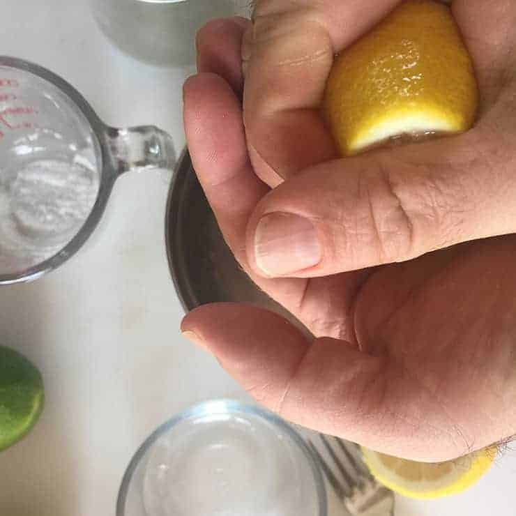 squeezing lemon into sweet and sour mix
