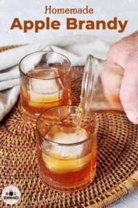 One full glass of apple brandy and one being poured into a glass placed on a wicker basket.