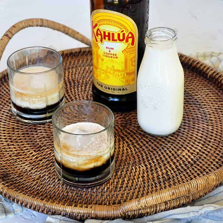 Two Classic White Russian cocktails on a platter with a container of milk and a bottle of Kahlua