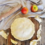 A Raw Pie Crust with apples in the pie. It is on a picnic table with two Braeburn apples, a rolling pin, and is laying on a cloth.