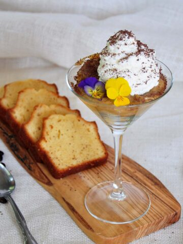 White Russian Mini Trifle on a cutting board with 4 pieces of vanilla bread. It is on a white cloth with a spoon and a grater.
