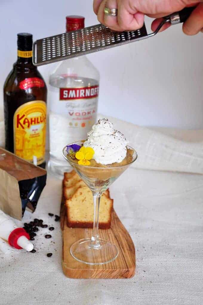 White Russian Mini Truffle with kahlua and vodka in the background. I am grating chocolate over the drink as a garnish.