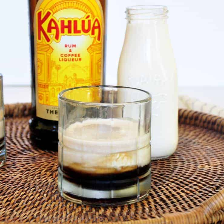 A Glass of Kahlua on a wicker platter with a contain of cream and kahlua in the background