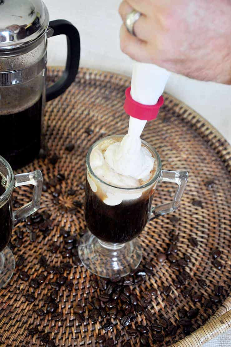 Placing Kahlua whipped cream on top of Russian coffee.