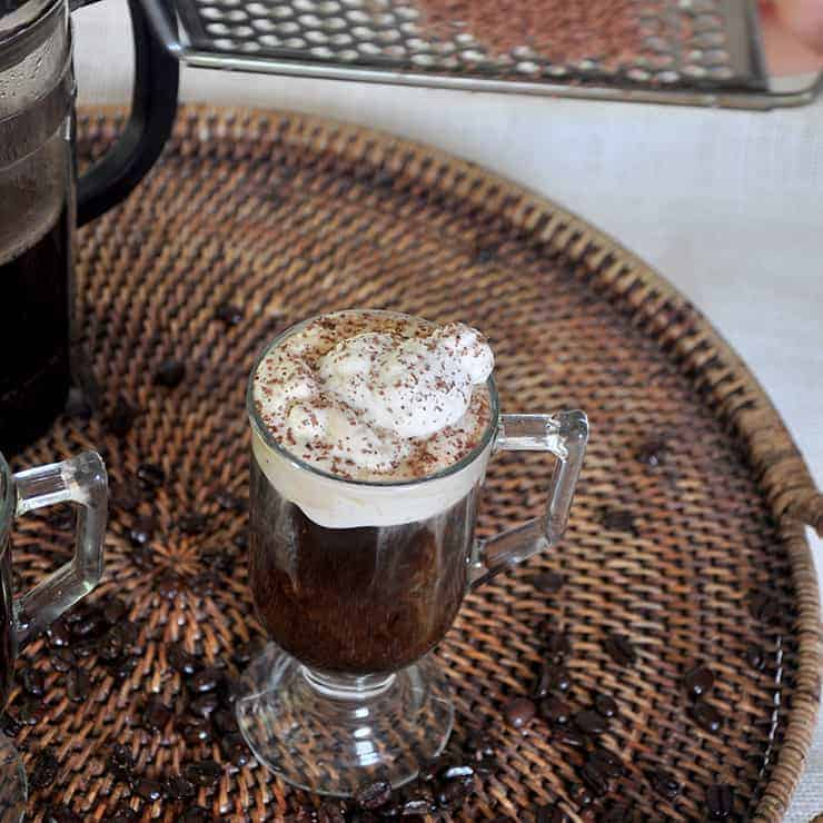Single Glass of our Russian Coffee recipe on a wicker platter that has coffee beans strewn throughout. I am grating some cocoa on top of the drink for flavor and garnish.