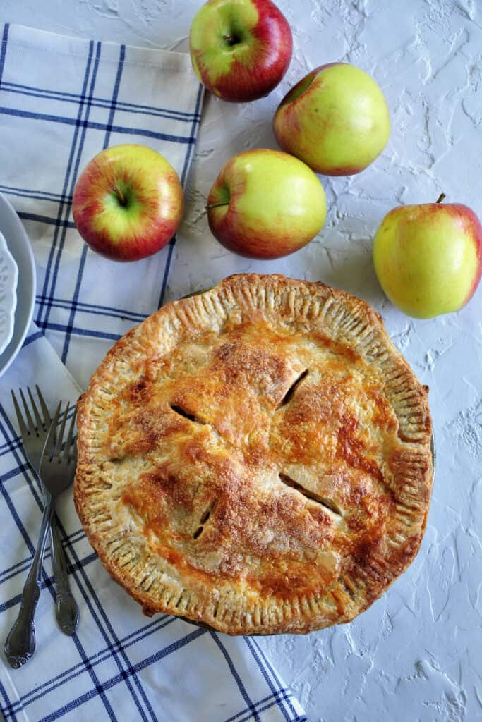 Vertical picture of a baked apple pie on a table with cloths, forks, and five Braeburn apples.