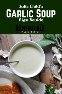 """""""Julia Child's Garlic Soup - Aigo Bouido"""" with a bowl of soup on wood with sage and garlic in the background."""