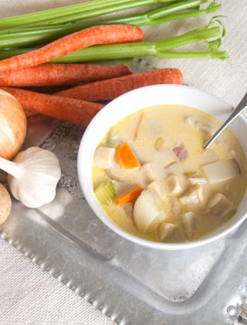 Bowl of Knephla Soup on a tin platter with garlic, onions, celery and carrots.