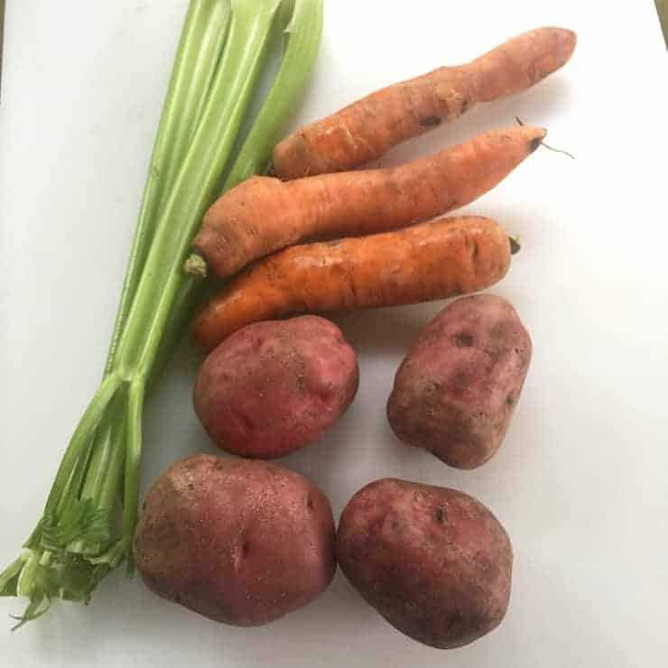 Celery, carrots and potatoes on a cutting board