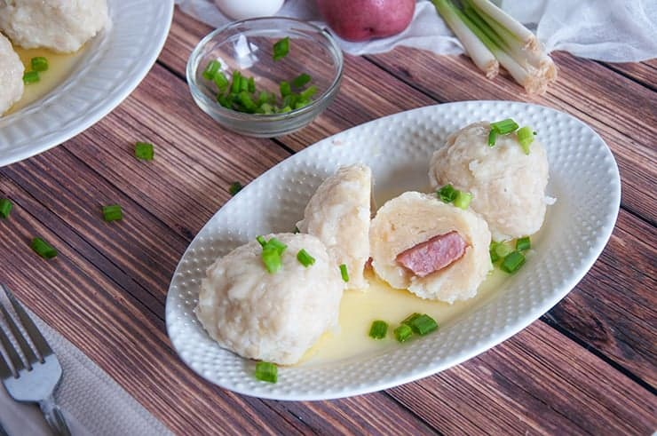 A Klubb Norwegian dumpling cut in half and exposing the ham that is in the middle.
